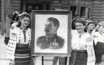 Girls in Ukrainian national clothing with a portrait of Stalin next to the Opera House