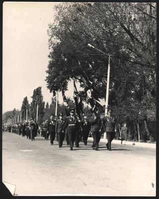 Колона ветеранів Другої світової війни  прямує по центральній вулиці до Вічного вогню